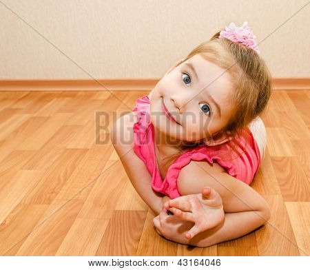 Funny Little Girl Lies On A House Floor