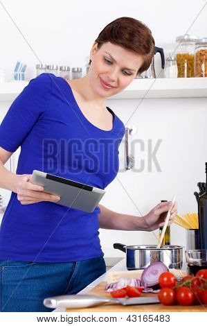 Woman Preparing Pasta Dish And Checking The Recipe On A Tablet