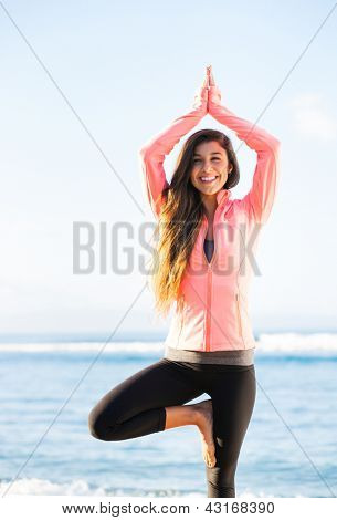 Young woman practicing morning meditation yoga in nature at the beach