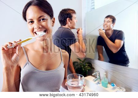 Bathroom routine for happy young couple brushing teeth and shaving in mirror