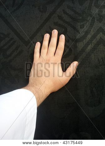 Kaaba Mecca in Saudi Arabia and Muslim pilgrims coming for Hajj, male hand touching the black Cover