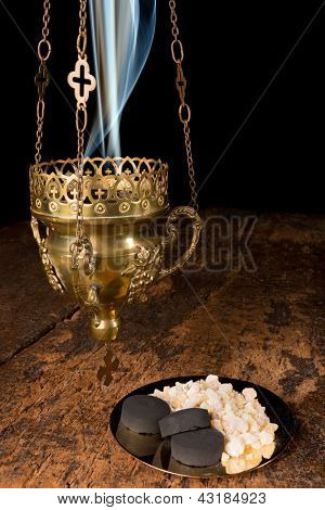 Smoking incense thurible and a golden plate with frankincense and charcoal pieces
