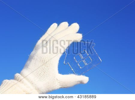 Hands in white gloves holding crystal house against blue sky.