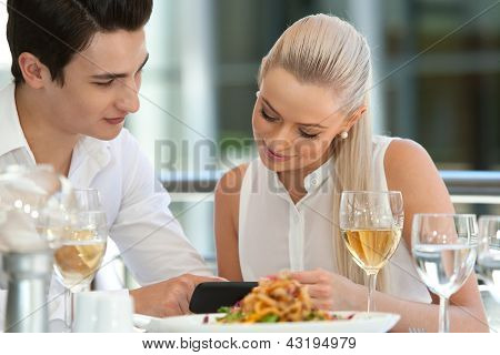 Cute Couple Looking At Smart Phone At Dinner.