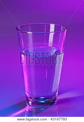 Glass with water on violet background