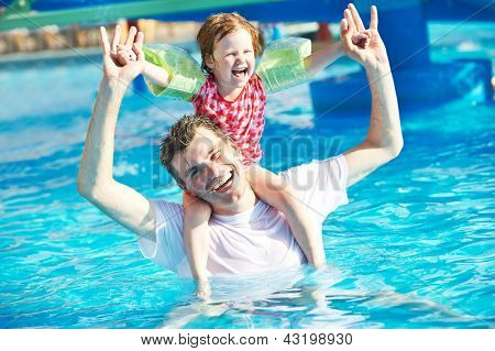 Happy smiling father man and child girl playing at water park in resort hotel swimming pool