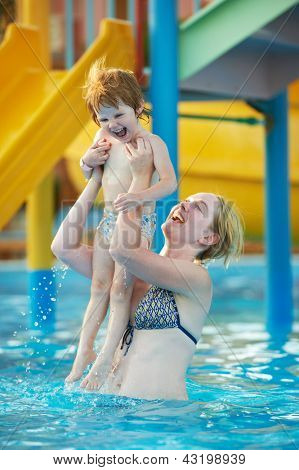 Happy smiling woman and child playing at water park in resort hotel swimming pool