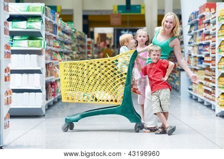 Family shopping. Woman and children with shop cart in supermarket store