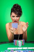 sexy young woman looking amazed at her unbelievable poker hand. on green background