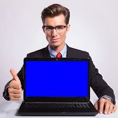 elegant young business man presenting a laptop and showing thumb up sign while looking at the camera