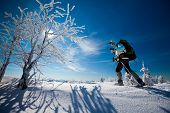 stock photo of snowy hill  - Hiker walk in snowshoes in winter mountains - JPG