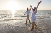 stock photo of retirement  - Happy senior man and woman couple dancing and holding hands on a deserted tropical beach at sunrise or sunset - JPG