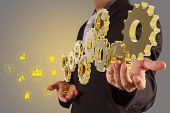 stock photo of hydroelectric  - businessman hand show 3d golden gear to success as industry concept - JPG