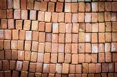 Wall of new red bricks stacked in rows.