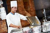 stock photo of food preparation tools equipment  - Adult arab chef man in uniform demonstrating food on cooker in resort hotel restaurant kitchen - JPG