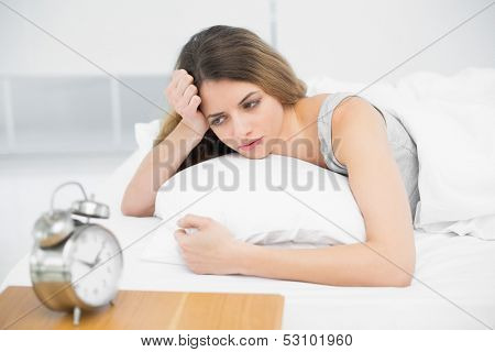 Calm attractive woman lying thoughtful on her bed in the bedroom