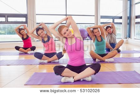 Portrait of fitness class and instructor sitting on yoga mats and stretching hands