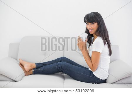 Gleeful young woman holding a cup sitting on couch smiling at camera