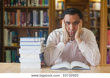 Handsome man sitting in front of an opened book in library looking bored at camera