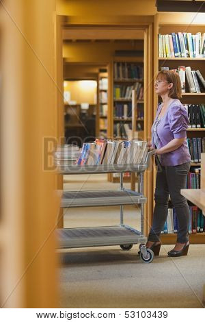 Serious female librarian pushing a cart in a library