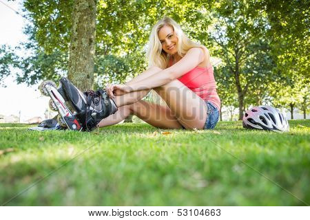 Casual smiling blonde putting on roller blades in a park on a sunny day