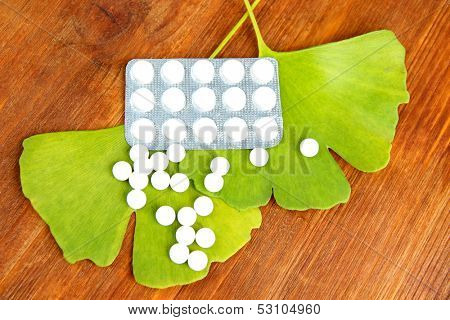 Ginkgo biloba leaves and pills on wooden background