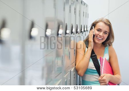 Cheerful pretty student phoning in school