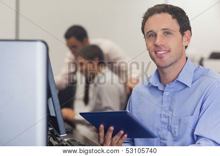 Male student holding a tablet sitting in front of computer in computer class