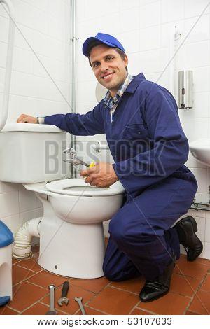 Good looking plumber repairing toilet in public bathroom
