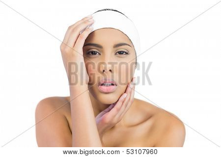 Stern nude brunette with hairband touching head on white background