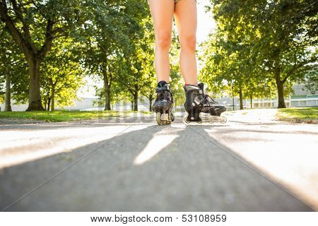 Close up of woman wearing inline skates standing on pathway in a park