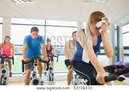 Determined and tired people working out at an exercise bike class in gym