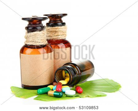 Ginkgo biloba leaves and medicine bottles with pills isolated on white