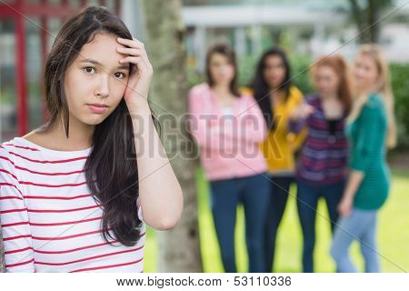 Portrait of a female student being bullied by other group of students