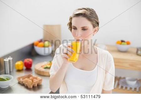 Lovely brunette woman drinking a glass of orange juice standing in her kitchen at home