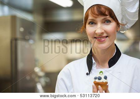 Pretty happy head chef holding blueberry dessert in professional kitchen