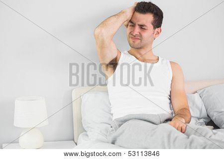 Wincing handsome man having a headache in bright bedroom