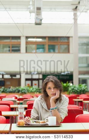 Gloomy female student sitting in the cafeteria with food tray