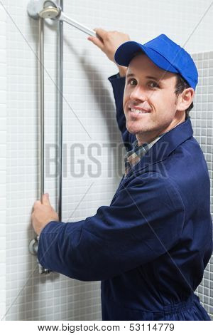 Smiling plumber repairing shower head in public bathroom