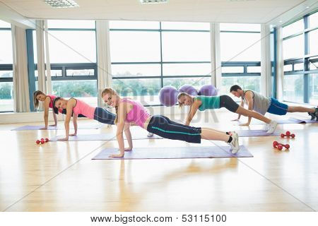 Side view portrait of trainer with class doing push ups in bright fitness studio