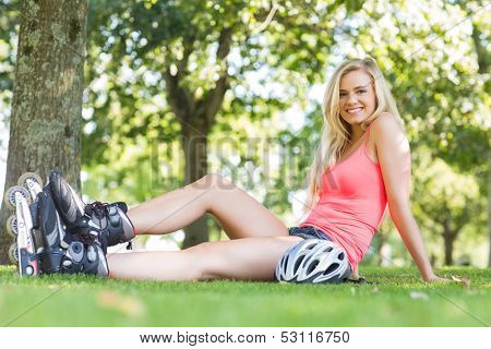 Casual smiling blonde wearing roller blades in a park