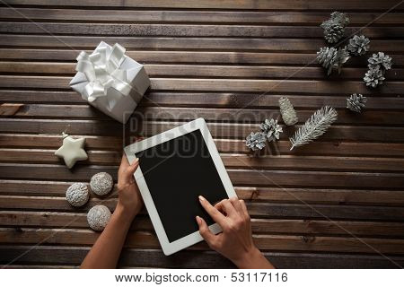 Image of three spice-cakes, decorative silver cones, giftbox and white toy star surrounding female hands touching display of digital tablet
