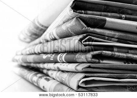 Closeup of newspapers on plain background