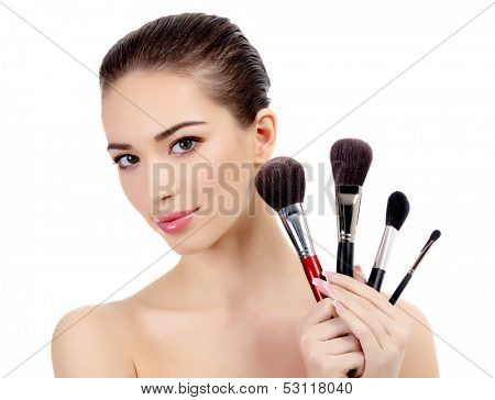 Pretty woman with cosmetic brushes, white background, copyspace
