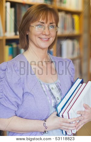 Female librarian posing holding some books smiling at camera
