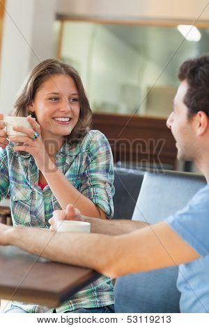 Two content students having a cup of coffee in college canteen
