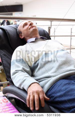Elderly Man Lies In Massage Armchair
