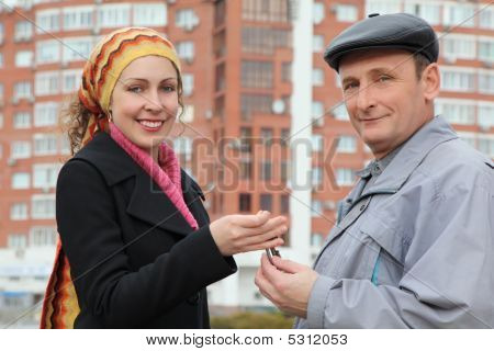 Young Smiling Woman Gives Keys Aged Man Against Building