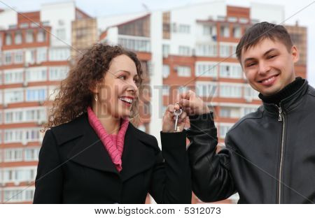 Young Couple With Key Against Many-storeyed House