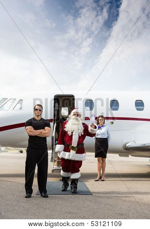 Santa exiting his modern sleigh with body guard.